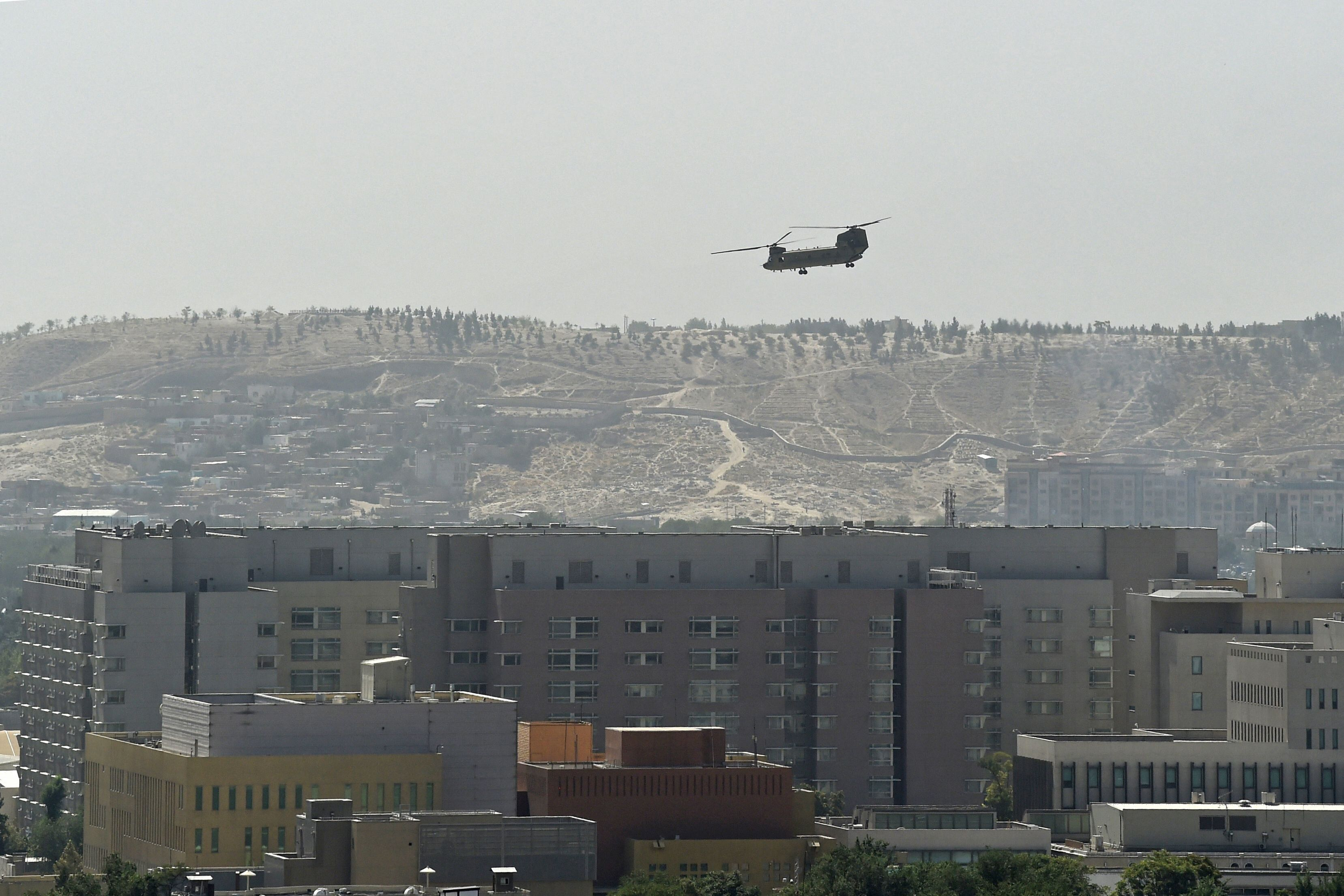 A U.S. Chinook military helicopter flies above the U.S. Embassy in Kabul on Aug. 15, 2021.