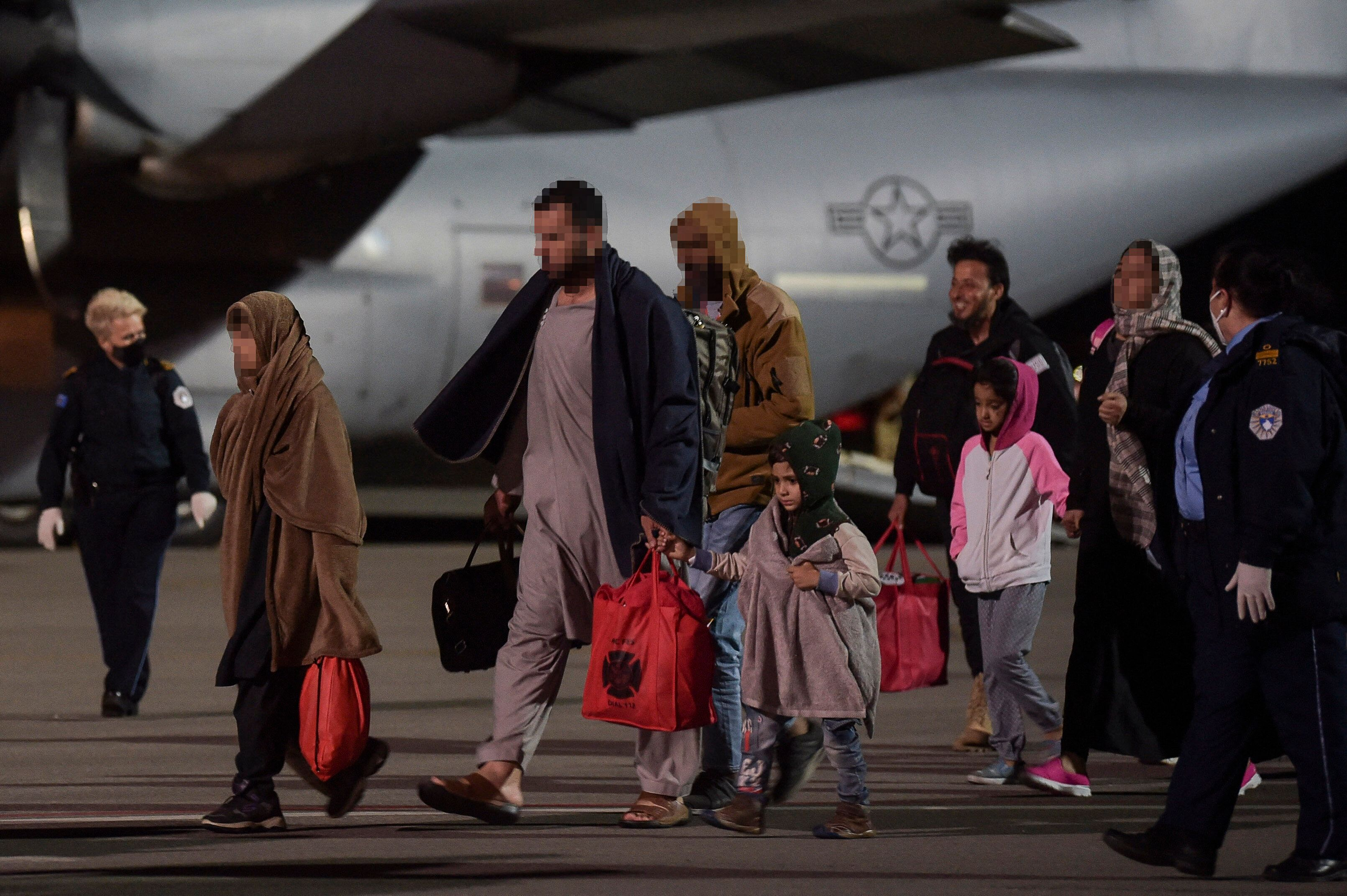 Afghan refugees exit a U.S. Air Force plane at Pristina International airport near Pristina, Kosovo, on Aug. 29, 2021.
