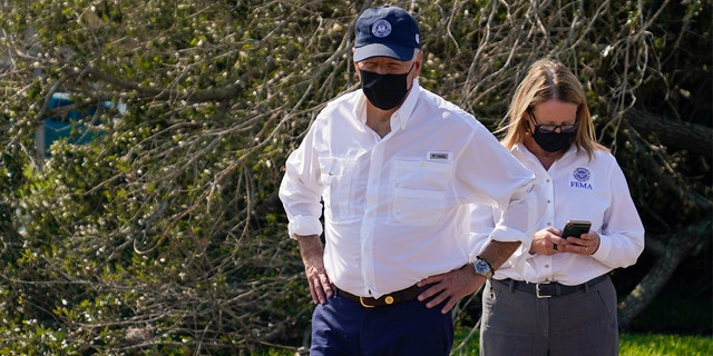 President Joe Biden pauses as he tours a neighborhood impacted by Hurricane Ida, Friday, Sept. 3, 2021, in LaPlace, Louisiana, as FEMA administrator Deanne Criswell checks her phone.
