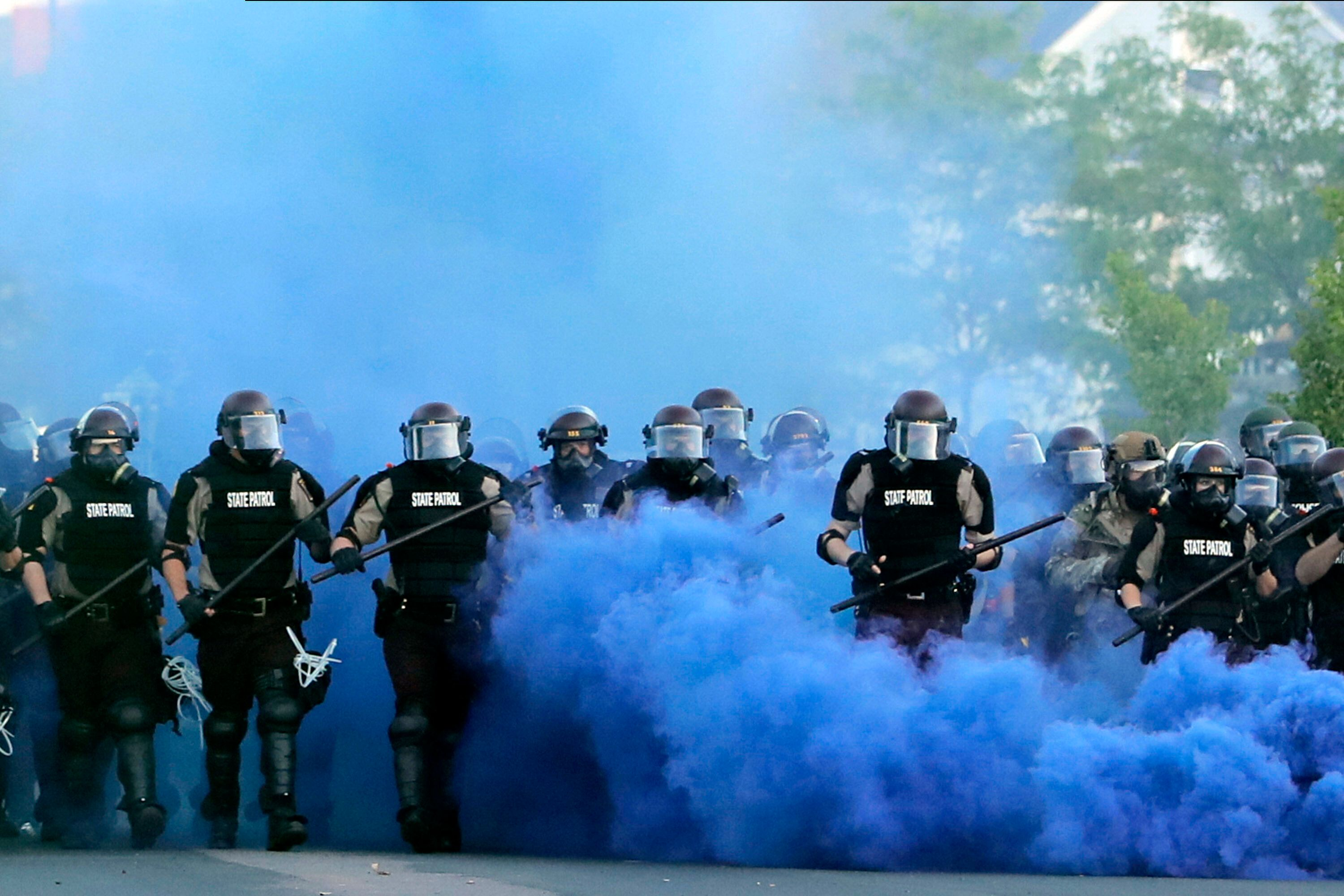 FILE - In this May 30, 2020, file photo, Minnesota State Police officers approach a crowd of protesters in Minneapolis. The M