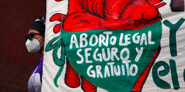 """A woman holds a banner reading, in Spanish, """"Legal, safe, and free abortion, legalize and decriminalize abortion now, for the independence and autonomy of our bodies,"""" as abortion-rights protesters demonstrate in front of the National Congress in Mexico City."""