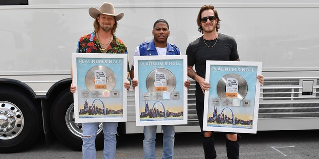 Brian Kelley and Tyler Hubbard of Florida Georgia Line and Nelly, center, take photos with their Platinum Single for 'LilBit' during CMT Crossroads: Nelly & Friends at The Factory At Franklin on September 01, 2021 in Franklin, Tenn.
