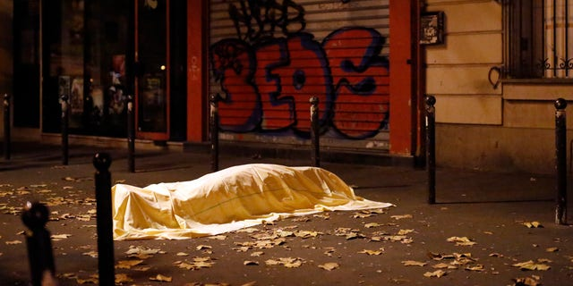 A victim of an attack in Paris lies dead outside the Bataclan theater in Paris, Nov. 13, 2015. In all, the attacks killed 130 people. (Associated Press)
