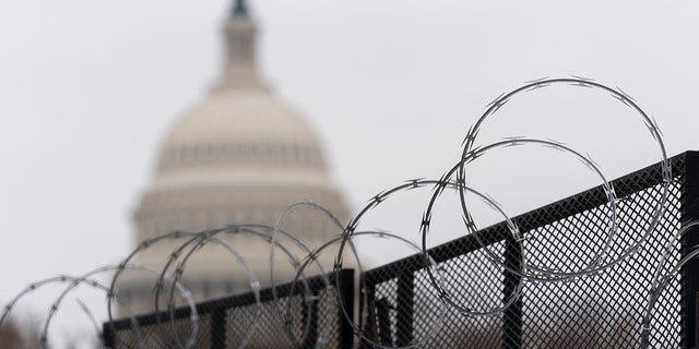The U.S. Capitol is seen behind the razor fence around the U.S. Capitol, Thursday, Feb. 18, 2021. U.S. Capitol Police officials told congressional leaders the razor-wire topped fencing around the Capitol should remain in place for several more months as law enforcement continues to track threats against lawmakers, a person familiar with the matter told The Associated Press on Thursday. (AP Photo/Manuel Balce Ceneta)