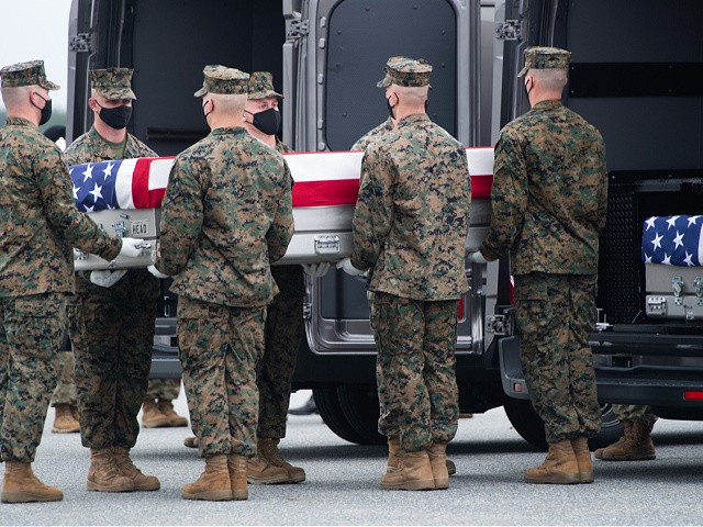 A flag-draped transfer case with the remains of a fallen service member are placed inside a transfer vehicle as US President Joe Biden attends the dignified transfer of the remains of a fallen service member at Dover Air Force Base in Dover, Delaware, August, 29, 2021, one of the 13 members of the US military killed in Afghanistan last week. - President Joe Biden prepared Sunday at a US military base to receive the remains of the 13 American service members killed in an attack in Kabul, a solemn ritual that comes amid fierce criticism of his handling of the Afghanistan crisis. Biden and his wife, Jill, both wearing black and with black face masks, first met far from the cameras with relatives of the dead in a special family center at Dover Air Force Base in Delaware.The base, on the US East Coast about two hours from Washington, is synonymous with the painful return of service members who have fallen in combat. (Photo by SAUL LOEB / AFP) (Photo by SAUL LOEB/AFP via Getty Images)