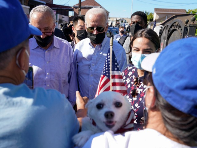 President Joe Biden talks with people as he tours a neighborhood impacted by flooding from the remnants of Hurricane Ida, September 7, 2021, in the Queens borough of New York, with Senate Majority Leader Chuck Schumer of N.Y., and Rep. Alexandria Ocasio-Cortez, D-NY, right. (AP Photo/Evan Vucci)