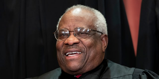 Associate Justice Clarence Thomas, appointed by President George H. W. Bush, sits with fellow Supreme Court justices for a group portrait at the Supreme Court Building in Washington, Friday, Nov. 30, 2018. Thomas was a regular participant in remote oral arguments during the COVID-19 pandemic after almost never asking questions to lawyers when the court heard its cases in person. (AP Photo/J. Scott Applewhite)