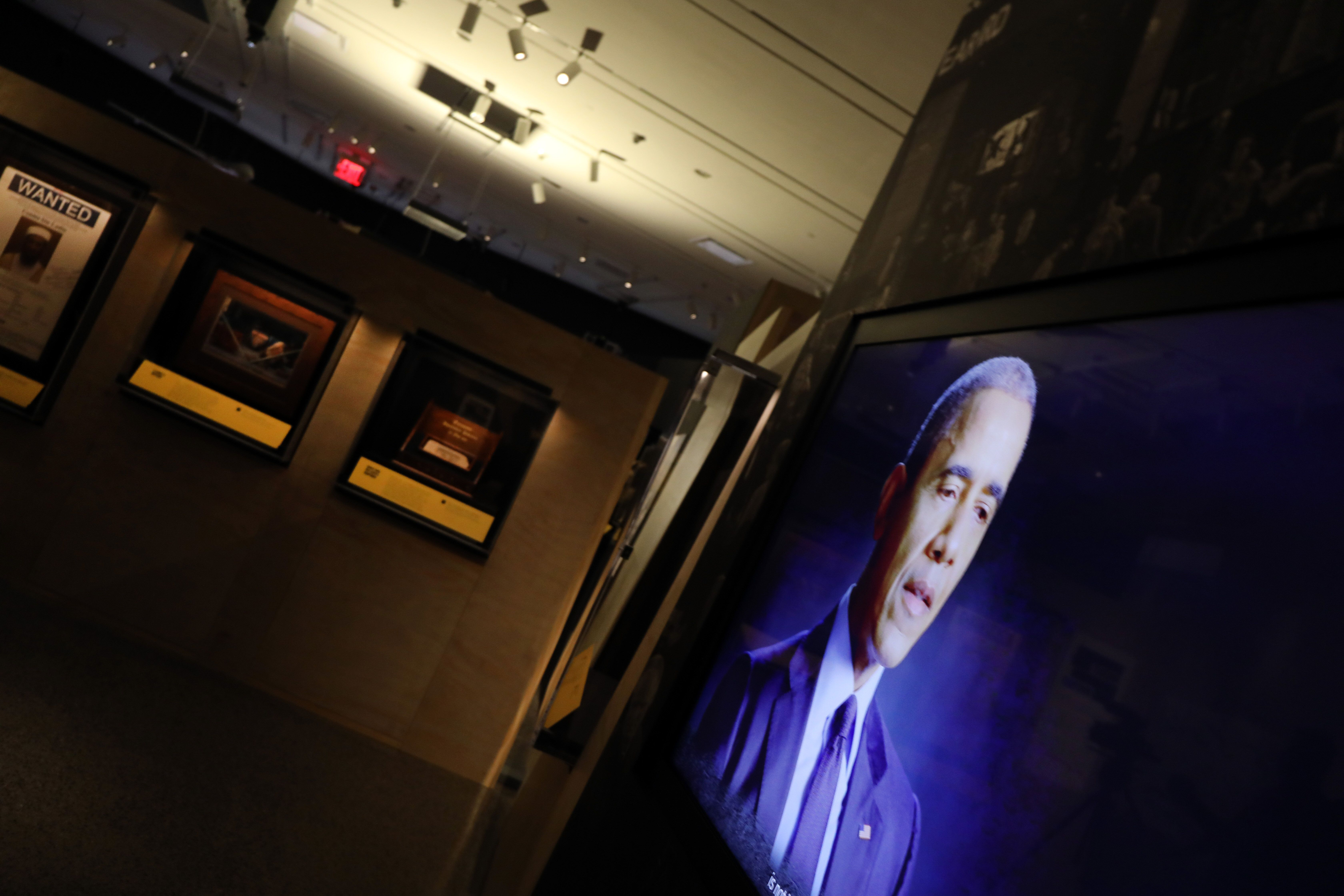 """A video of former president Barack Obama shows on a monitor at the exhibition """"Revealed: The Hunt for Bin Laden"""" at the 9/11"""