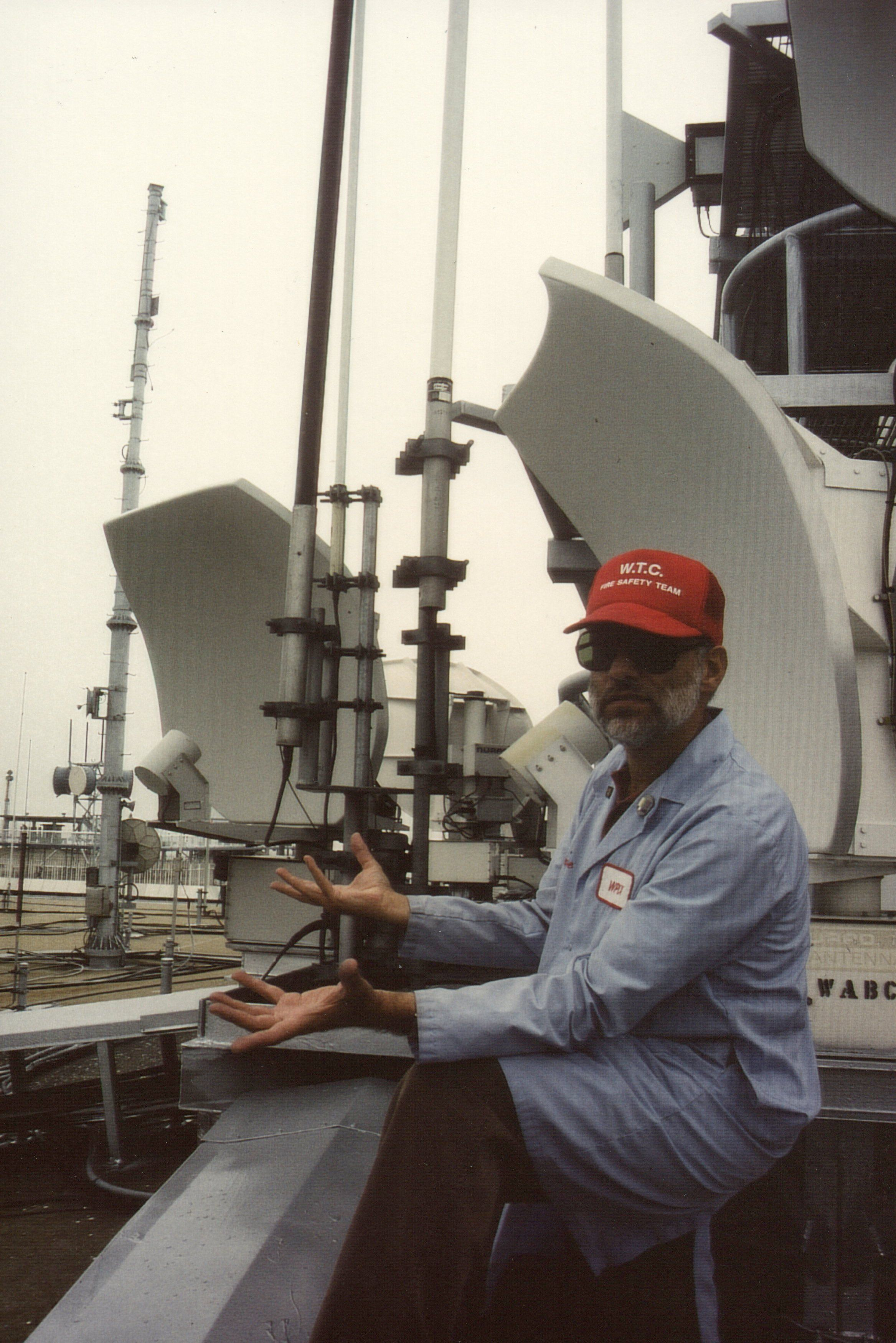 Steven Jacobson perched on the roof of One World Trade Center, pointing out the repeater transmitters, circa 1981.