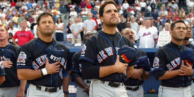 Left fielder Joe McEwing #47, shortstop John Valentin #4, catcher Mike Piazza #31, third baseman Edgardo Alfonzo #13 and right fielder Jeromy Burnitz #20 of the New York Mets hold their FDNY and NYPD hats over their hearts during the national anthem before the second game of a MLB double-header against the Atlanta Braves on September 11, 2002 at Turner Field in Atlanta, Georgia. The Mets shut out the Braves 5-0.