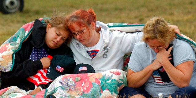 ADVANCE FOR PUBLICATION ON SUNDAY, SEPT. 5, AND THEREAFTER - FILE - In this Wednesday, Sept. 11, 2002 file photo, from left, Shannon Barry, Lisa Starr and Michelle Wagner, all of Hershey, Pa., comfort each other as they listen to a memorial service for victims of Flight 93 near Shanksville, Pa. President Bush will lay a wreath at the crash site later in the day to mark the anniversary of the terrorist attacks.