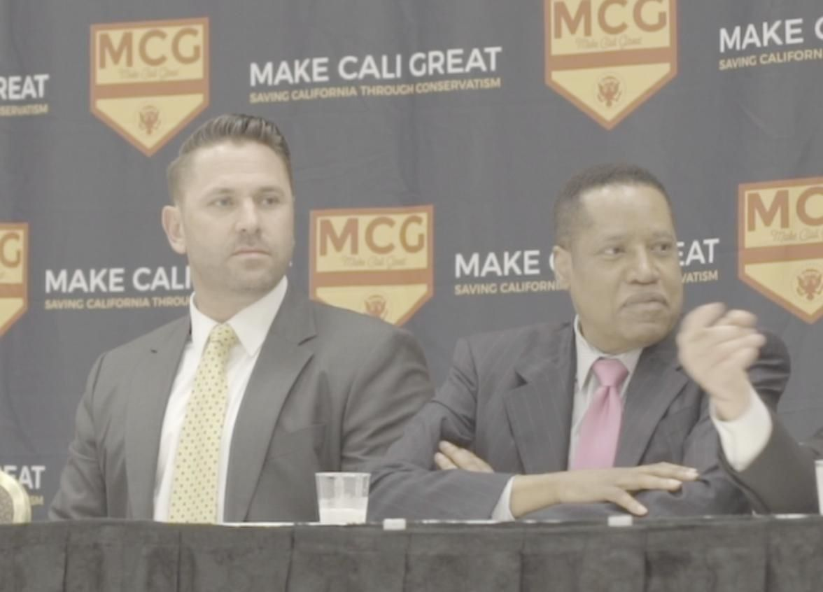 """Larry Elder (right) sits next to Kyle Chapman, a white nationalist, during a panel discussion at the """"Summer of Conservatism"""""""