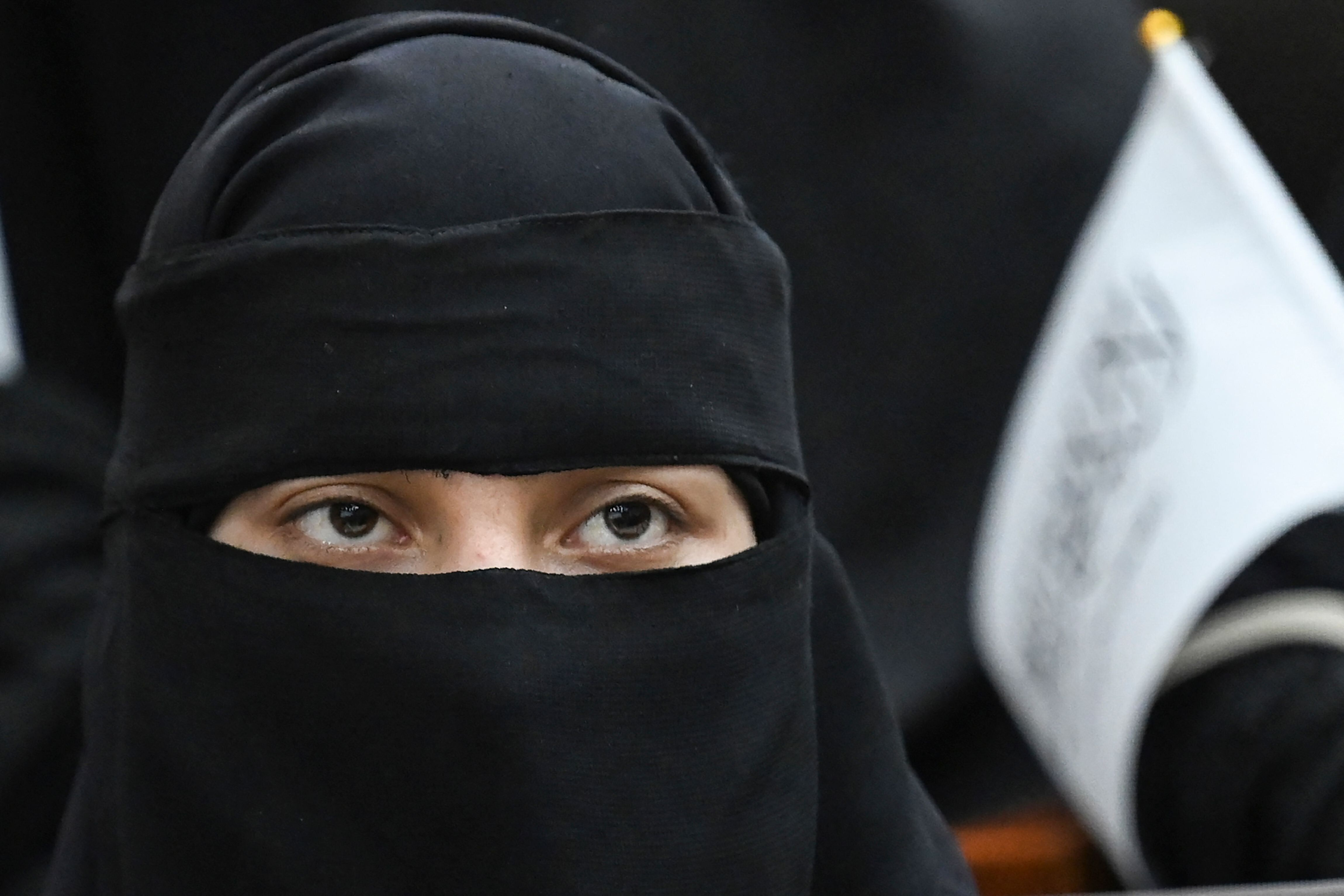 A veiled student holds a Taliban flag while listening to a speaker before a pro-Taliban rally at the Shaheed Rabbani Educatio