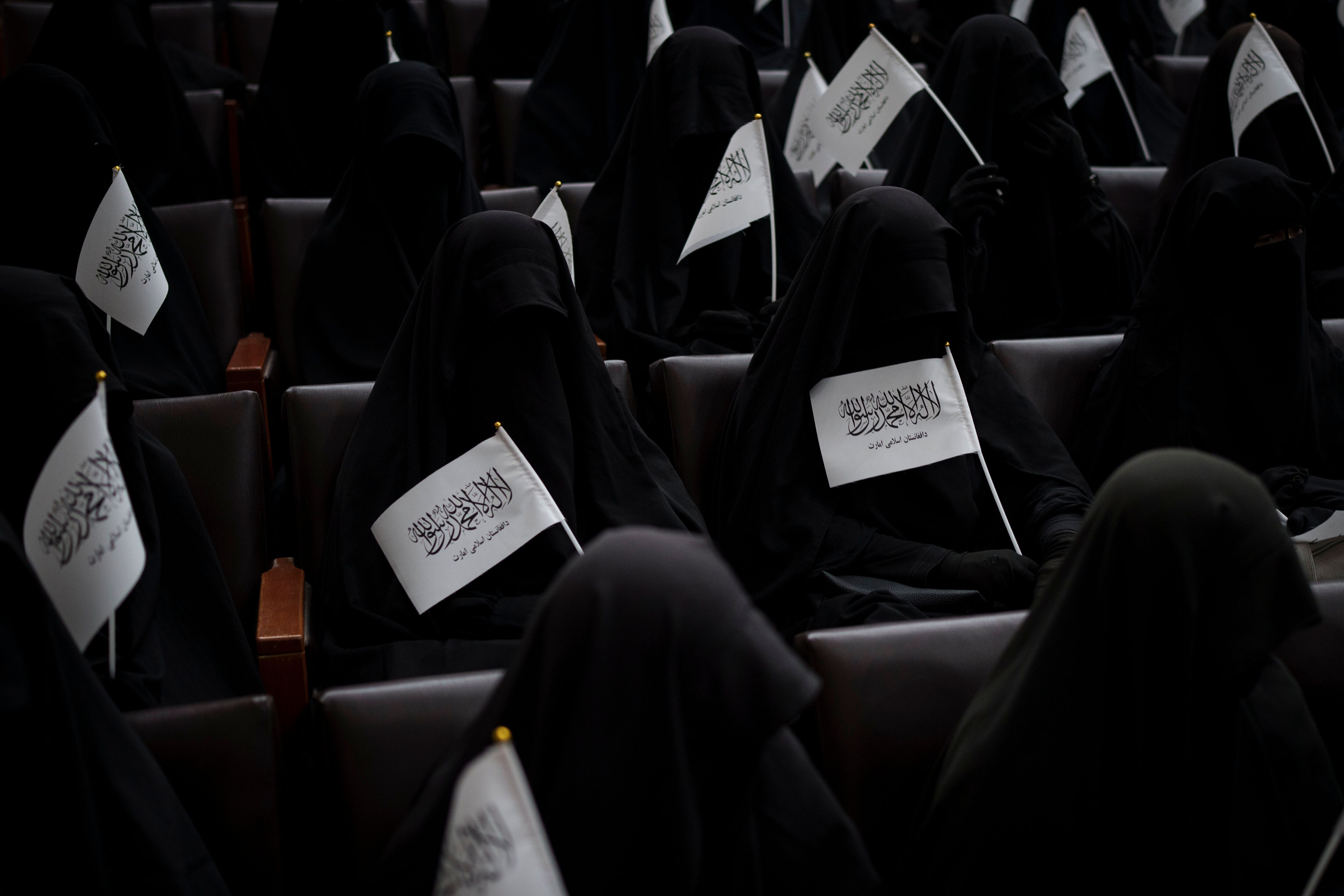 Women wave Taliban flags as they sit inside an auditorium at Kabul University's education center during a demonstration in su