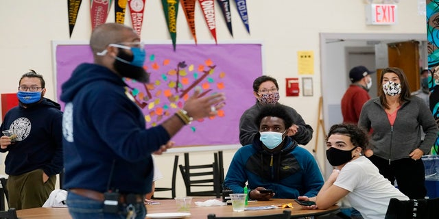 Students, teachers, administrators and counselors listen as principal Malik Lewis, foreground, second from left, teaches them a history lesson at West Brooklyn Community High School on Oct. 29, 2020, in New York.