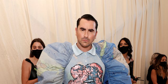 Dan Levy appears in a fantastical getup with puffy shoulders.