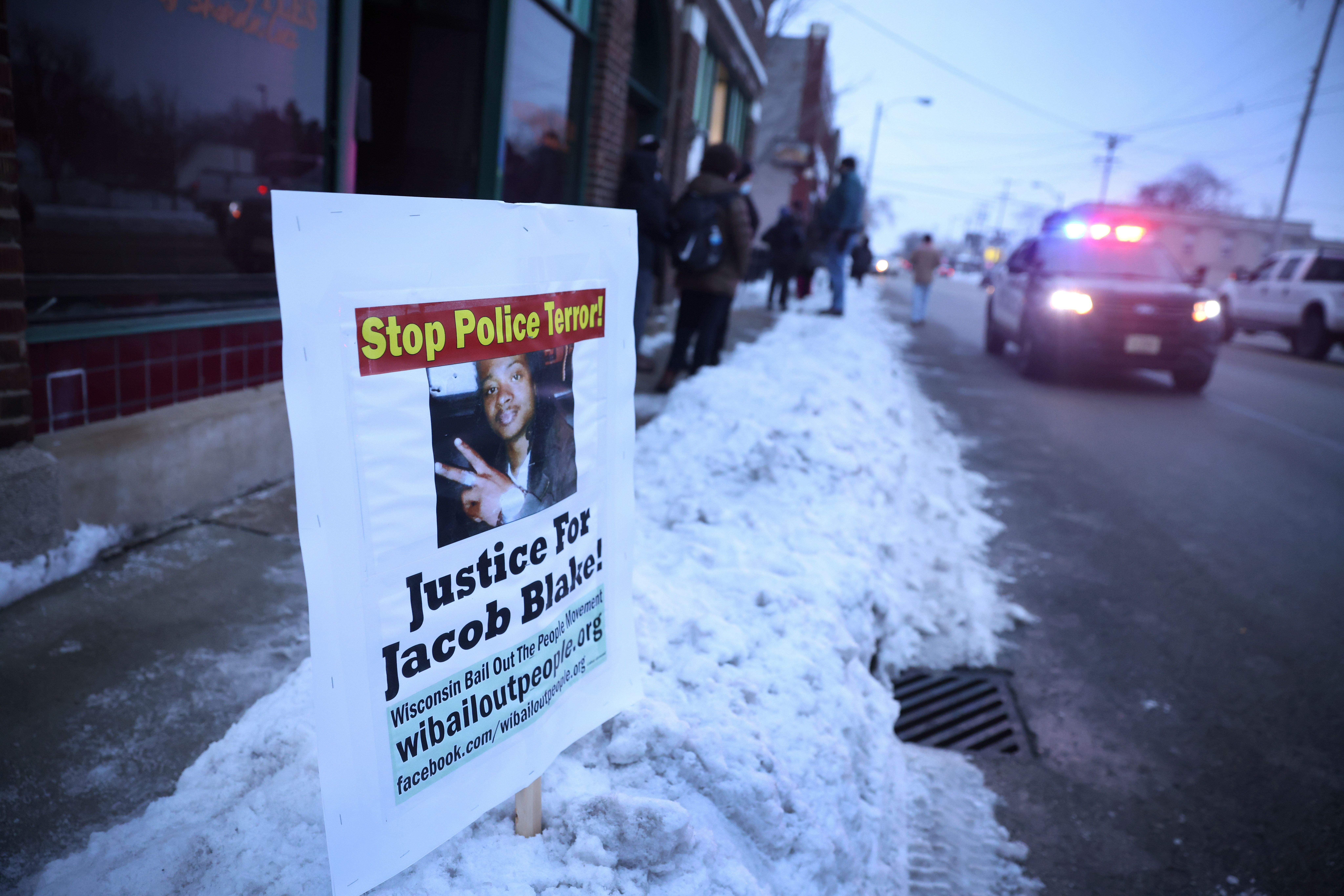 A police car drives past a sign showing support for Jacob Blake Jr., who was shot seven times in the back by a Kenosha police