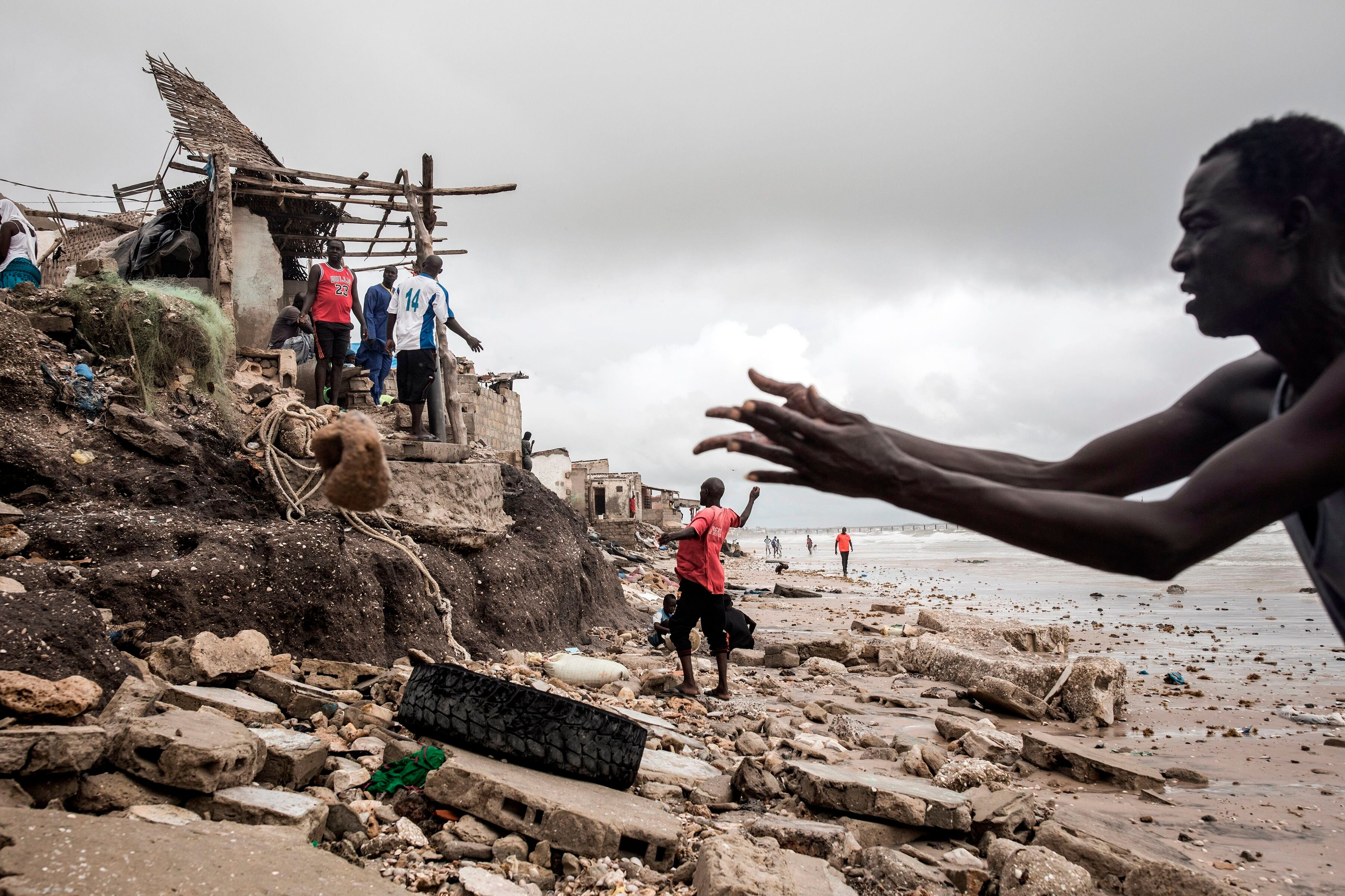 A man repairs his makeshift barrier to protect his house before the next high tide arrives in Bargny, Senegal, on Sept. 3, 20