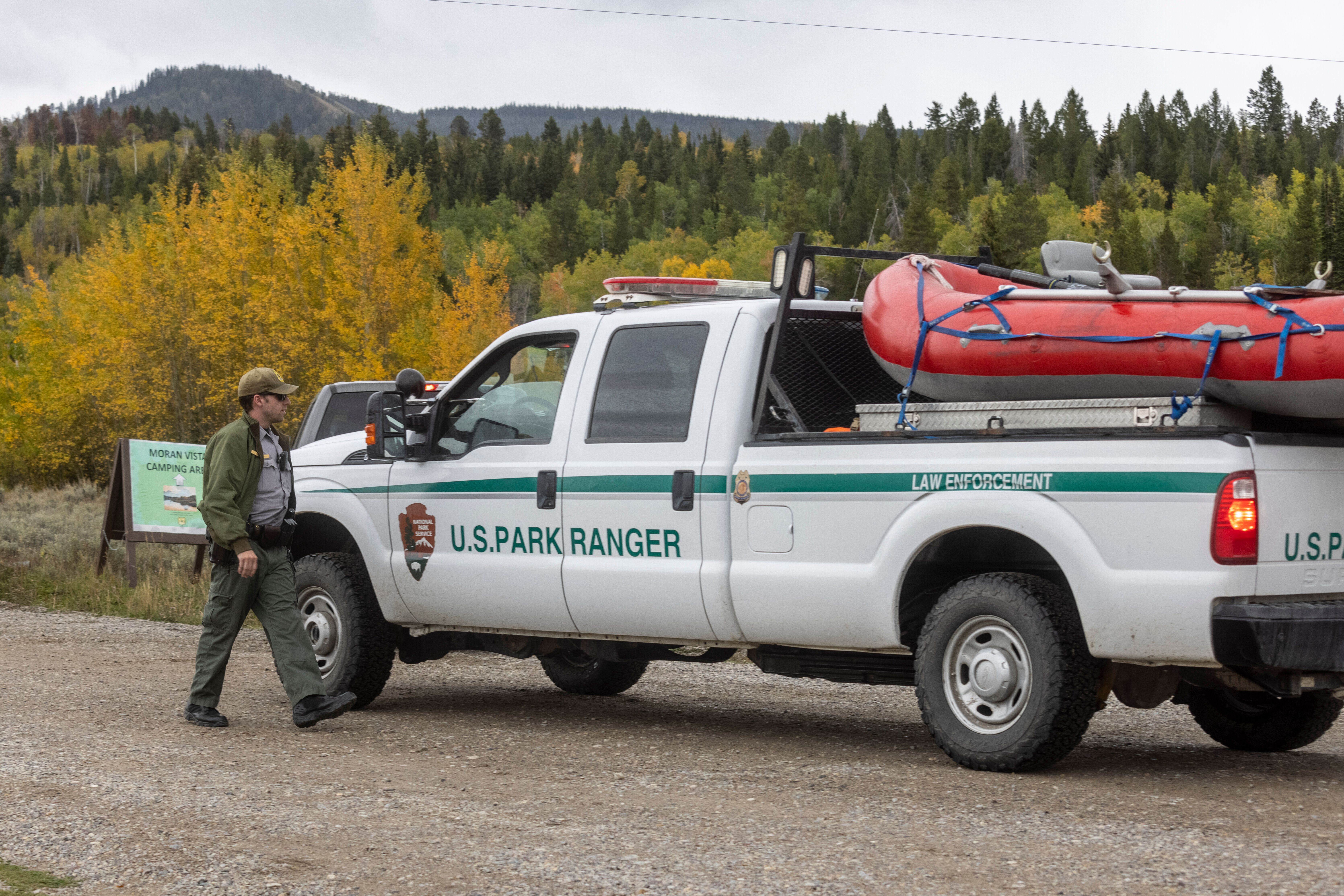 A park ranger speaks with a colleague on the road to Spread Creek Campground on Sunday near Moran, Wyoming. Law enforcement s