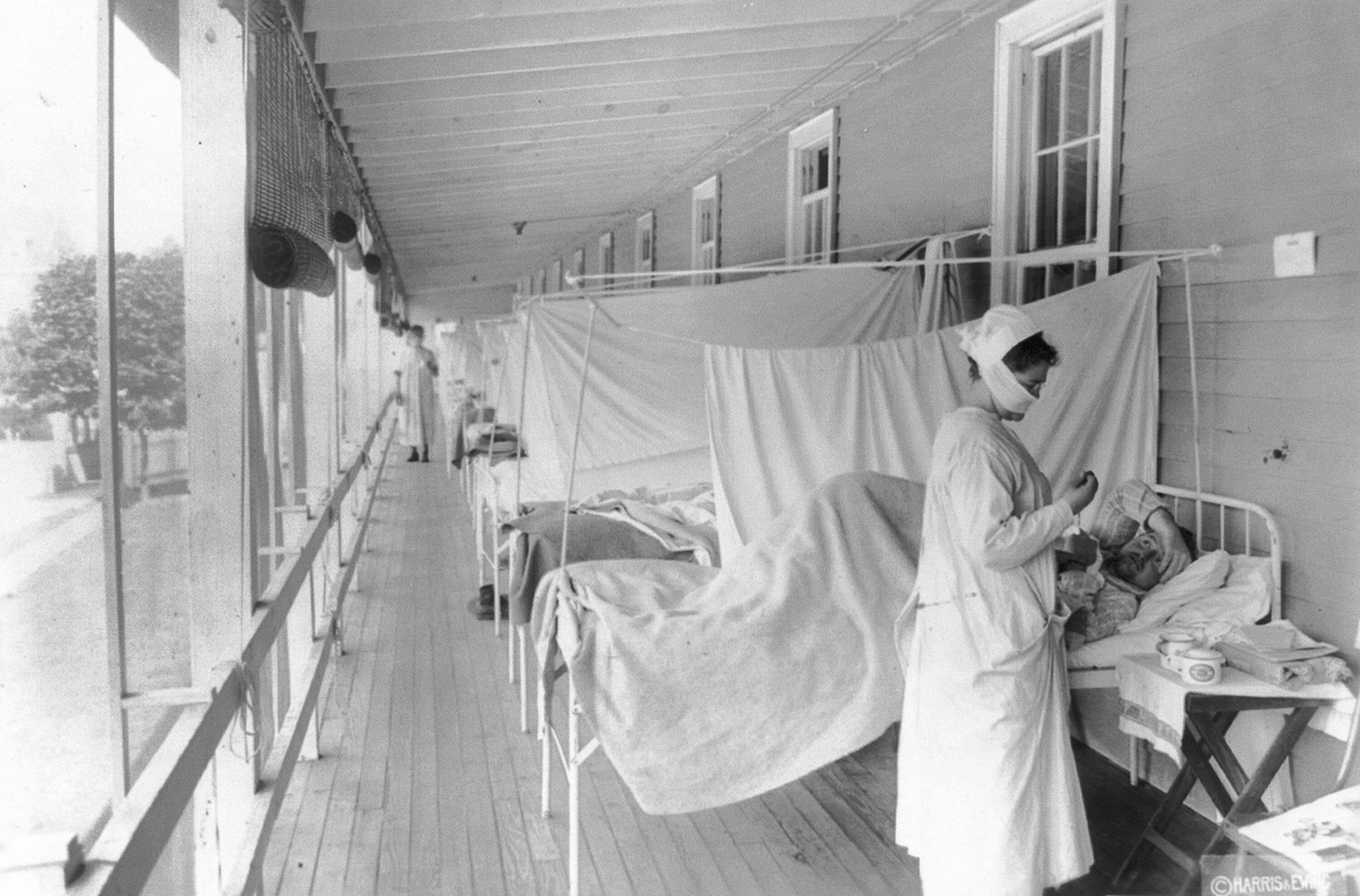 In this November 1918 photo made available by the Library of Congress, a nurse takes the pulse of a patient in the influenza