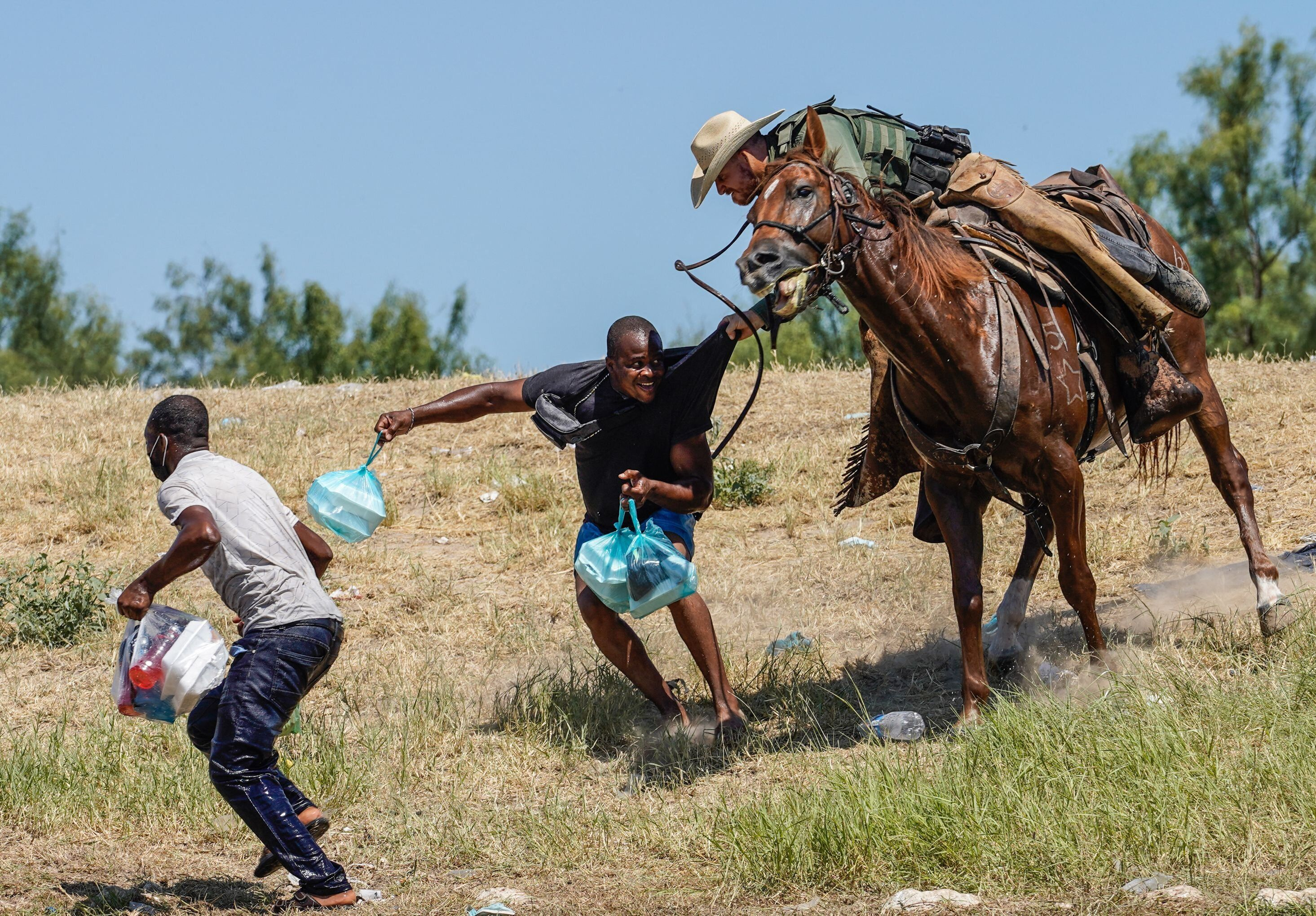 A Border Patrol agent on horseback tries to stop a Haitian migrant from entering an encampment in Del Rio, Texas, on Sept. 19