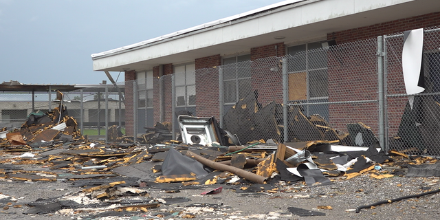 The school yard at South Lafourche High School is filled with debris from Hurricane Ida.