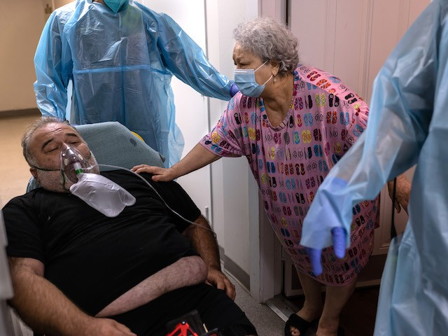 A mother says goodbye to her son, who had severe coronavirus symptoms, as medics from the Houston Fire Department EMS transport him to a hospital on August 16, 2021 in Houston, Texas. (John Moore/Getty Images)